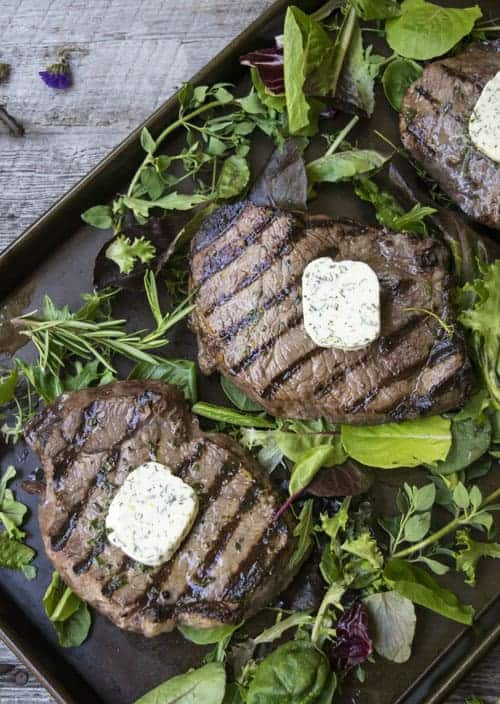Easy Grilled Sirloins are perfect for any summer cook out! This recipe starts the night before with a dry brine, and finished with an herb butter!
