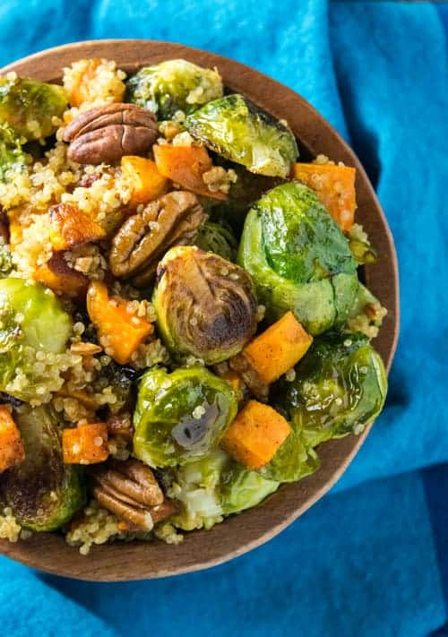 This Easy Fall Quinoa Bowl recipe is packed with roasted brussel sprout, sweet potatoes, quinoa, pecans, and topped with an apple cider vinaigrette. It's an easy dinner recipe, and perfect for meal prepping. | The Hungry Waitress