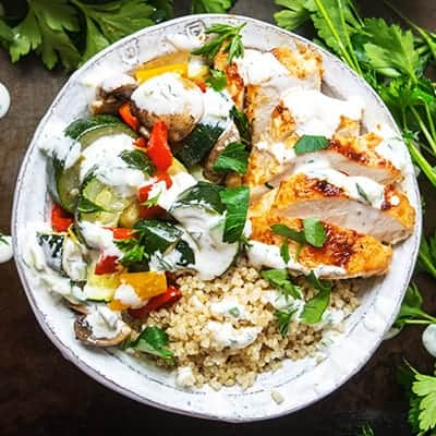 Healthy Greek Chicken Bowl drizzled with Cucumber Yogurt Sauce