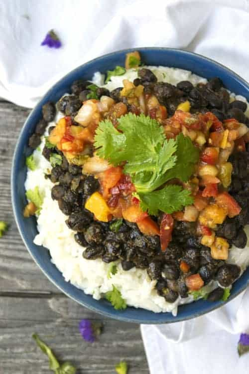 Spiced Black Beans and Coconut Rice topped with mango peach salsa is surprisingly an easy summer pantry meal. Whip this easy dinner recipe up in no time.