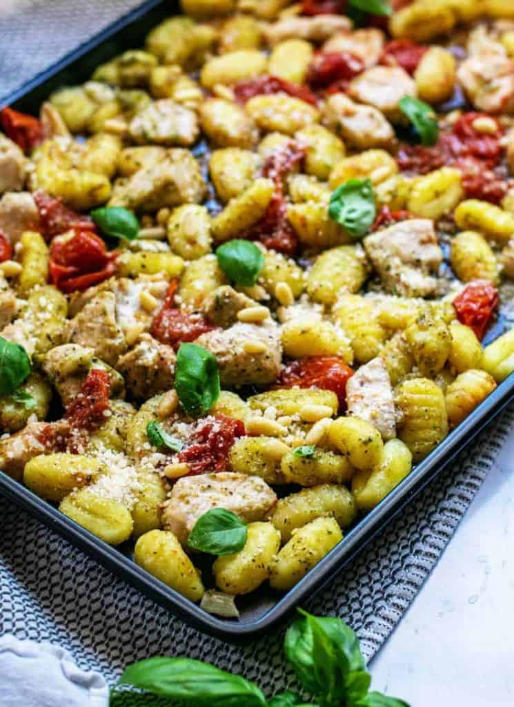 close up of sheet pan full of chicken, gnocchi, and vegetables