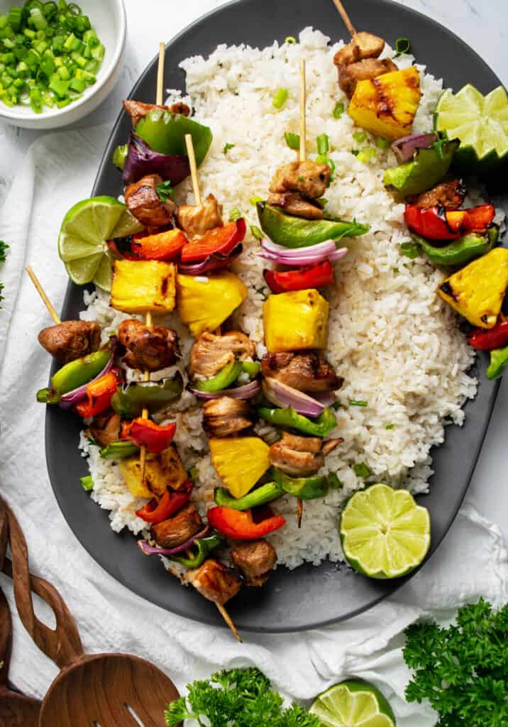 Huge platter of coconut rice with Grilled Pineapple Chicken Kabobs on top