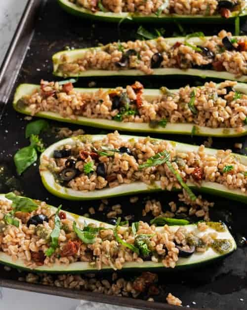 pan full of zucchini boats with farro and sun dried tomatoes with pesto