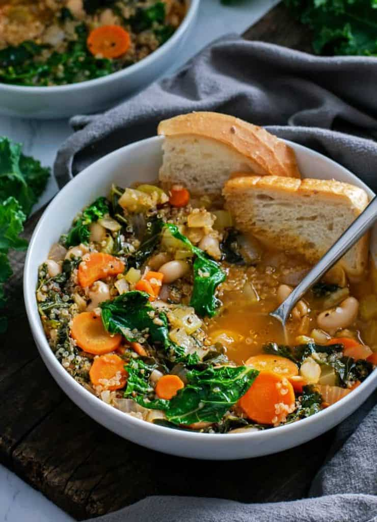 Crunchy sourdough bread dipped in  Vegan White Bean and Kale Soup