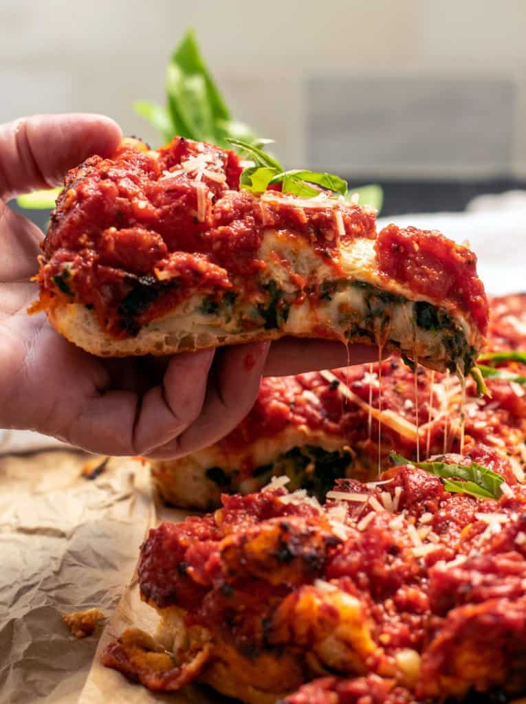 cheesy slice of vegetarian spinach stuffed pizza