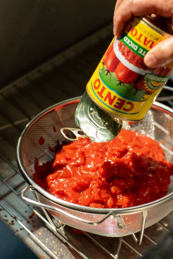draining canned tomatoes